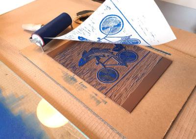 Druckprozess, Farbwalze, Linolplatte: Fisch mit Fahrrad und Wein für Linoldruck/Kunstdruck