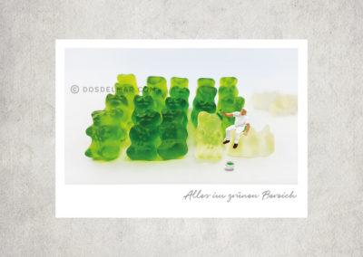 Postkarte Kleine Freiheit, Miniaturwelten, Miniaturfotografie. Miniaturfigur malt weiße Gummibärchen mit grüner Farbe an.