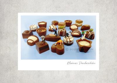 Postkarte Kleine Freiheit, Miniaturwelten, Miniaturfotografie. Miniaturfiguren arbeiten an Schokoladenpralinen – kleine Dankeschön
