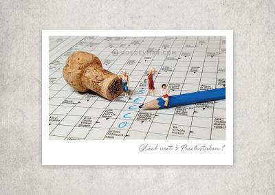 Postkarte Kleine Freiheit, Miniaturwelten, Miniaturfotografie. Miniaturfiguren auf Kreuzworträsel mit Sektkorken, Stift, Secco, Sekt, Glück.